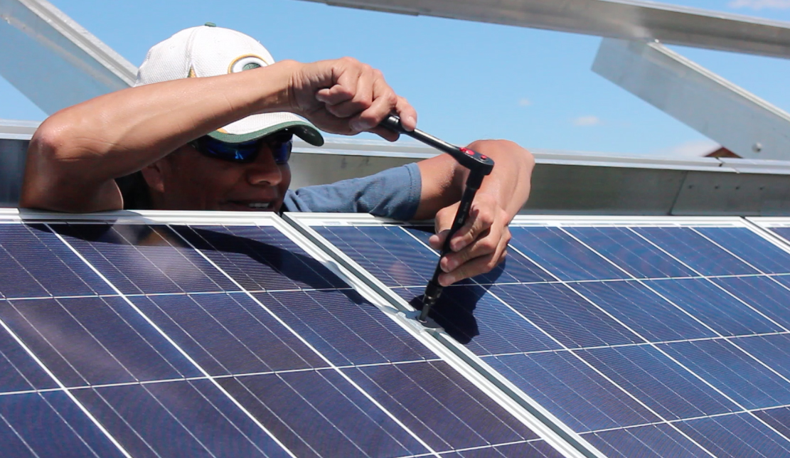 Chris Crow Shoe installing solar panels on the Piikani Nation reserve