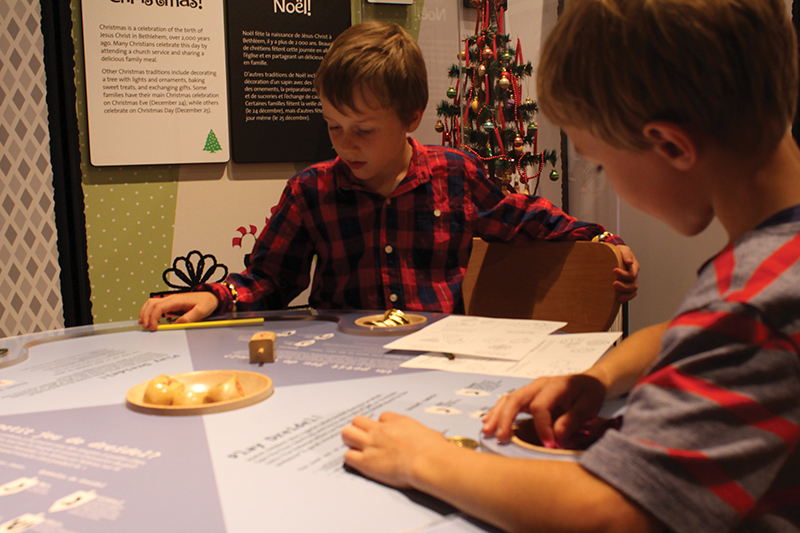 Dominic (left) and Julien Benoit play the dreidel game at the new Kids Celebrate! exhibition at the Galt Museum and Archives.